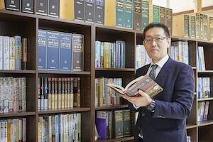 小林弁護士が本を持っている写真