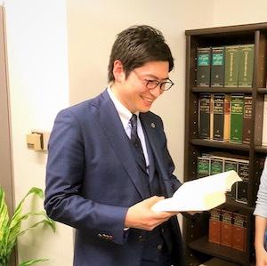 六法を読んでいる久貝弁護士の写真